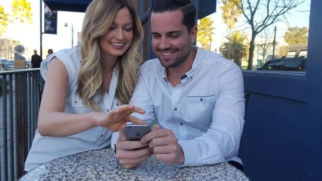 カフェのテーブルに座りひとつのスマートフォンを2人で仲良く覗き込むカップル