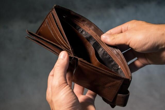 残金1円の革の長財布の中を覗き込む男性の手