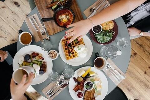 小さなテーブルの上いっぱいに並んだおいしそうな朝ごはんとそれを囲む人たち