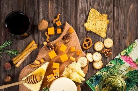 ウッドボードの上におしゃれに並べられたチーズやスナック、ナッツたち