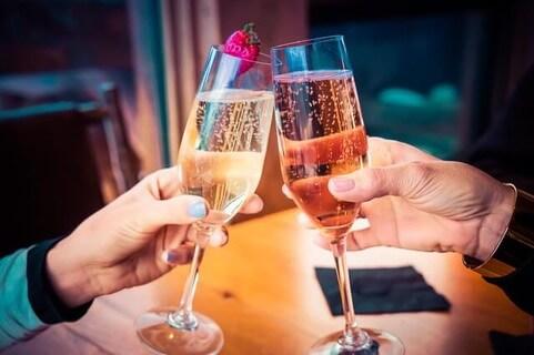 2人きりの空間を楽しむべくシャンパンでカンパイをするカップル