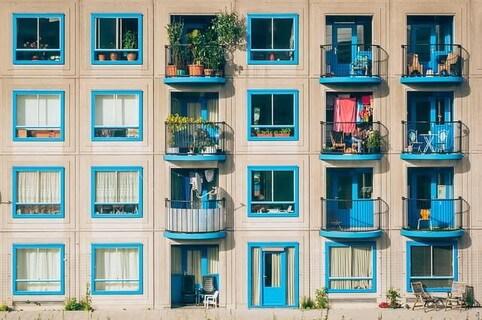 人それぞれの楽しみ方がうかがえる青い窓のフレームが可愛いアパートの小さなバルコニー