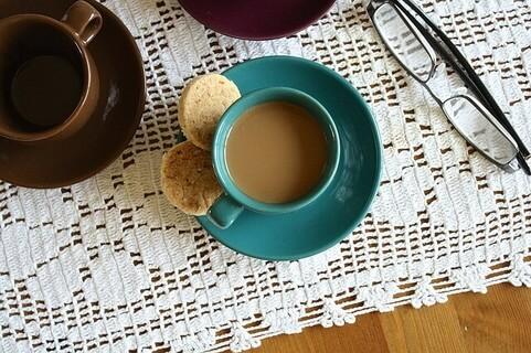テーブルの上に置かれたメガネとおしゃれな器に注がれたコーヒー