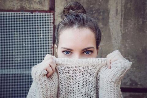 白いセーターを引き上げて顔を隠す青い目の女性