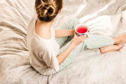 ルームウェアを着てベッドの上に座りハーブティーを飲んでリラックスする女性