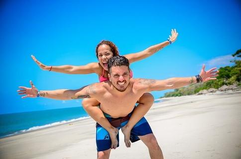 真っ青な空のした白い浜辺で楽しそうにはしゃぐカップル
