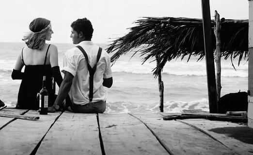 海辺のポーチに腰かけワインを楽しむカップル
