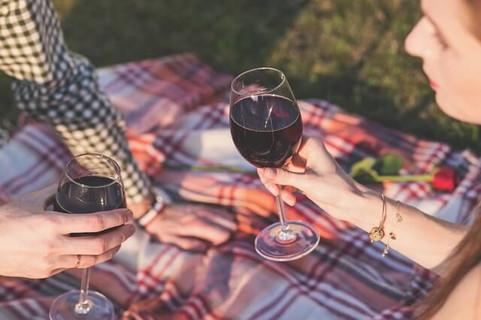 日が傾く中レジャーシートの上に座り赤ワインでカンパイするカップル