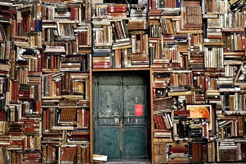 古めかしいドアと壁のようにぎっしりと積まれた本
