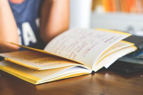 肘をついて机の上の本に没頭する女性