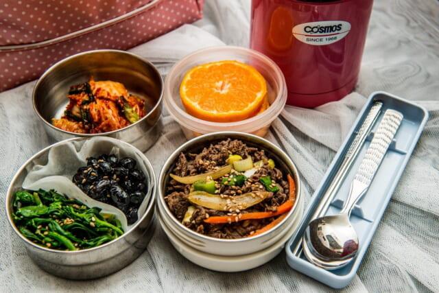おにぎりや漬物、唐揚げ、焼き魚など笹の葉に包まれたおいしそうなお弁当