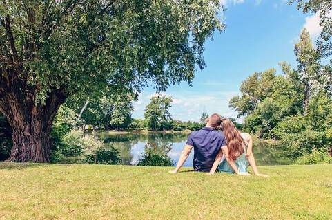 湖のほとりに腰かけ体を寄せ合う仲良しのカップル