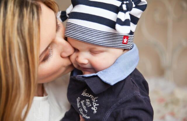 赤ちゃんを抱きあげまぶたにキスをする子供好きで優しい女性
