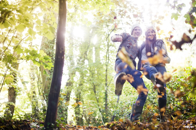 林の中で落ち葉を蹴り上げてはしゃぐ楽しそうなカップル