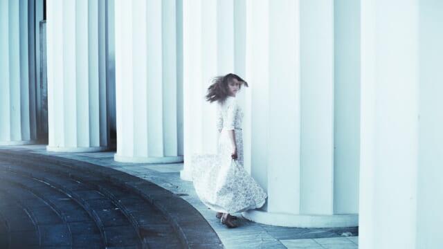白い柱が立ち並ぶ中、ドレスを身にまとい髪をなびかせて振り向く女性