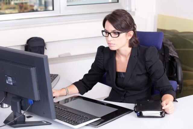 黒いスーツに黒ぶちのメガネをかけパソコンと向き合う真面目そうな女性