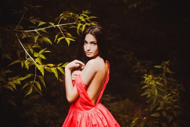 背中のファスナーをあけて赤いドレスを脱ごうとするスタイルが良い女の子