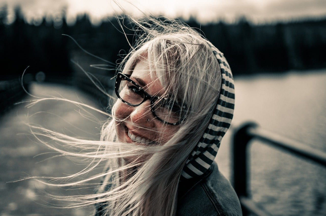 髪をなびかせて満面の笑顔で振り返るメガネがキュートな女性