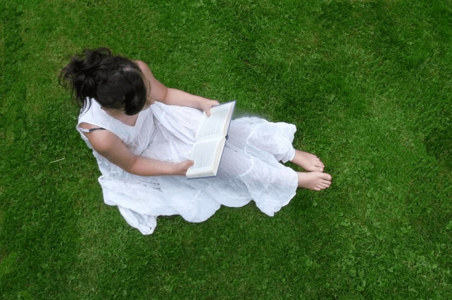 まっ白なワンピースを着て、青い芝生の上に座り読書をする清楚な印象の女の子
