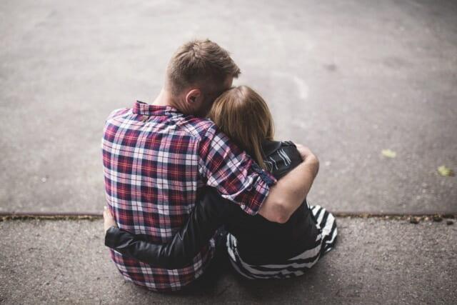 道端に座り小柄で可愛らしい雰囲気の女性を抱きしめる男性