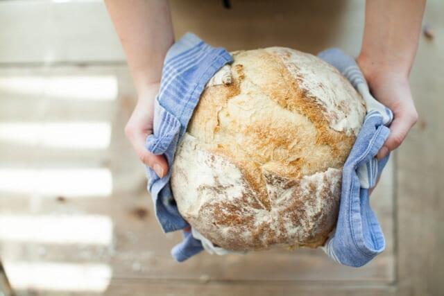 焼きたての手作りのパンを差し出す家庭的な女性の手