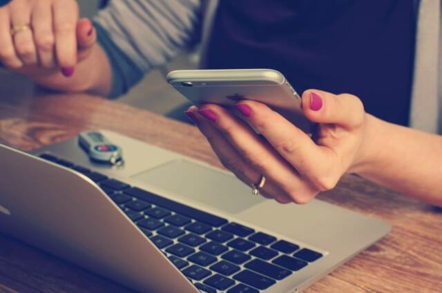 スマートフォンとPCで家計簿を管理するしっかりものの女性