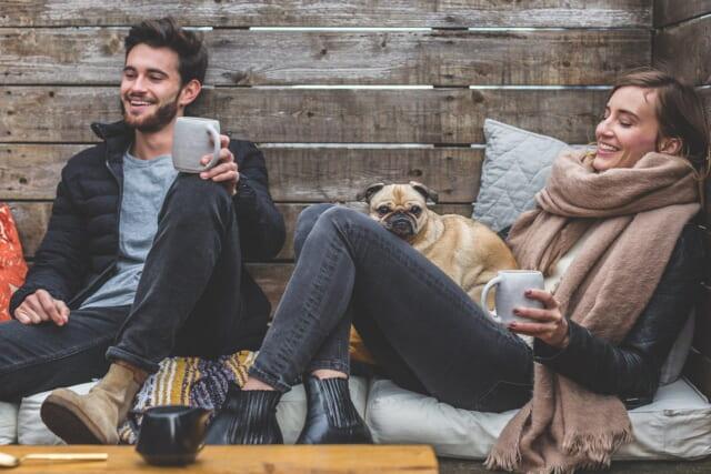 コーヒーカップを片手に椅子に腰を下ろし、居心地良さそうに談笑するカップル