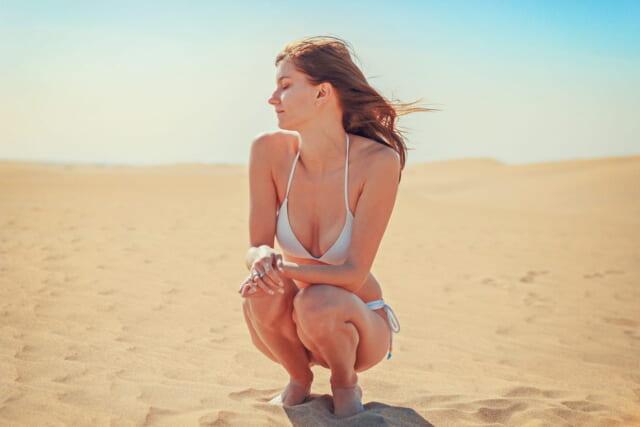 白いビキニを着て砂浜にしゃがみこむ年齢の若い女性