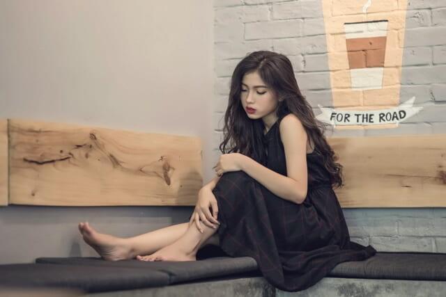 ソファに座り悲しそうにうつむくなかなか彼氏ができない女性
