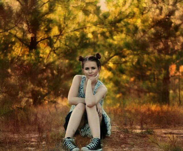木漏れ日の中地面に座り頬に肘をついて考え事をする女の子