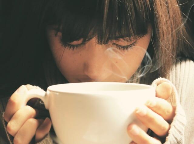 うつむき気味で両手で白いコーヒーカップを持ち口をつける黒髪がきれいな女の子