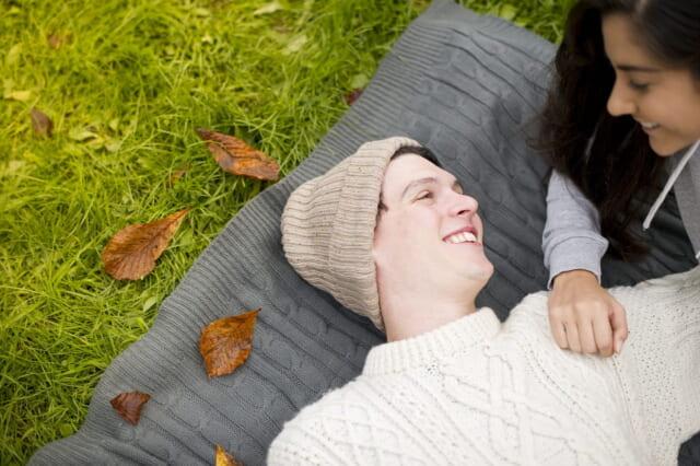 草むらにシートを引き寝転がり恋人の顔を見て穏やかに微笑む男性