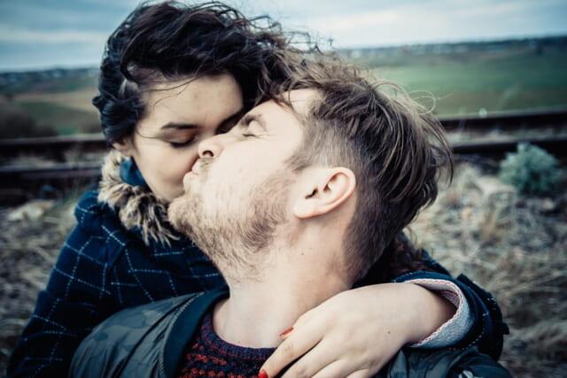 ビーチの砂浜に腰かけ恋人の肩を揉んであげる思いやりがある男性