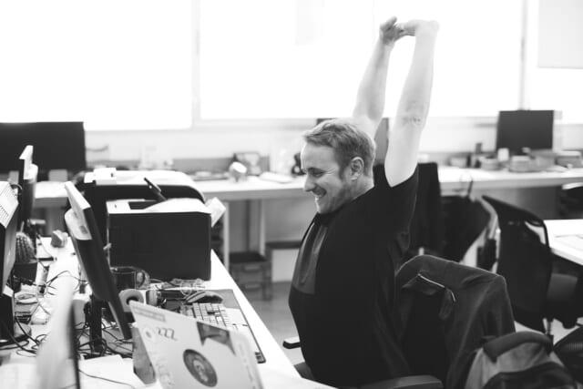デスクの前で伸びをして仕事の息抜きをする男性