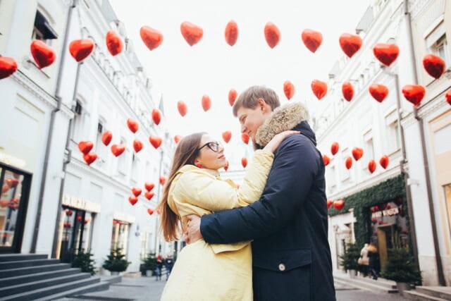 赤いハートの風船が並ぶ街で恋人と向かい合い愛を誓う男性