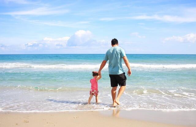 小さい女の子の手を取り青く広がる海の波打ち際を歩く家庭的なお父さん