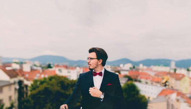 ヨーロッパの街並みを背景にスーツに赤いチョウネクタイを付けたメガネがおしゃれな男性