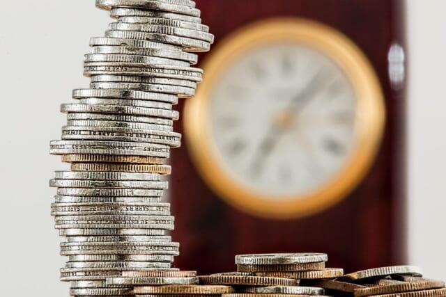 価値観の違いが大きく影響するお金と時間を連想させる積み重なったコインと時計