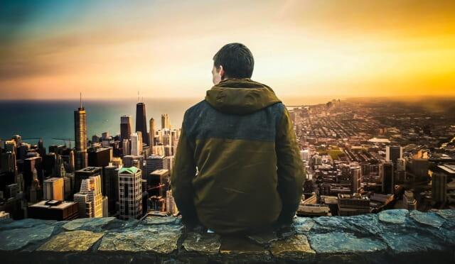 青空に突き出た岩山の上に立ち地平線を眺めるひとりぼっちの男性