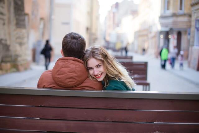 理想の彼氏の隣に腰かけ満面の笑みで振り返る女性