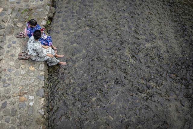 川辺に腰を下ろし下駄を脱いで足を流れにつけて涼む浴衣姿のカップル
