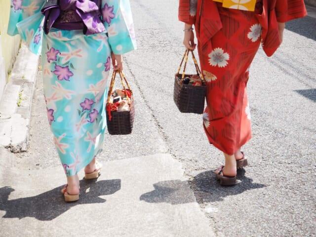 浴衣を着て小幅でちょこちょこと歩く2人の女の子