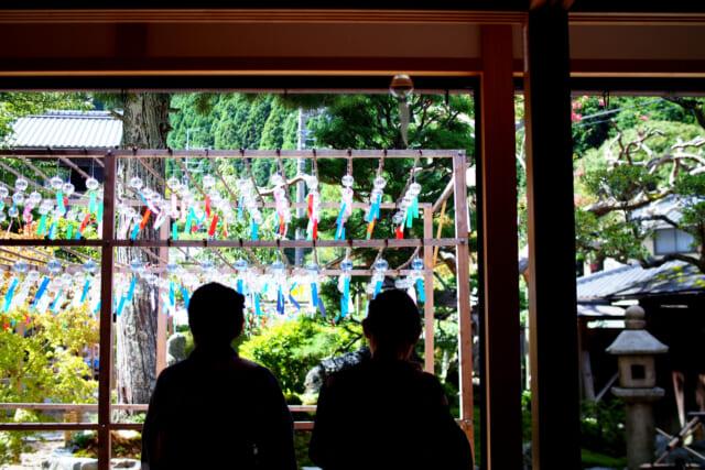 縁側に座り、涼しげな風鈴が並ぶ庭を眺める浴衣姿の2人の女性