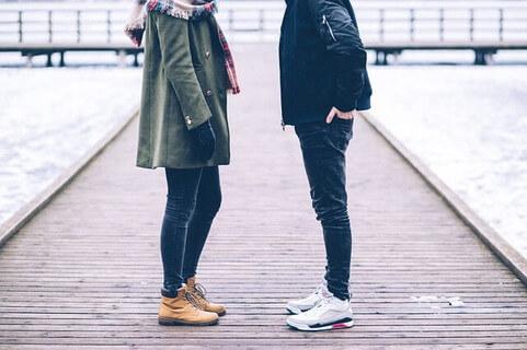橋の上に向かい合って立つ顔が見えない男性と女性