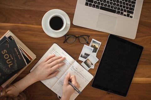 机の上にパソコンとノートを広げ、何度も何度も文章を書きなおす女性