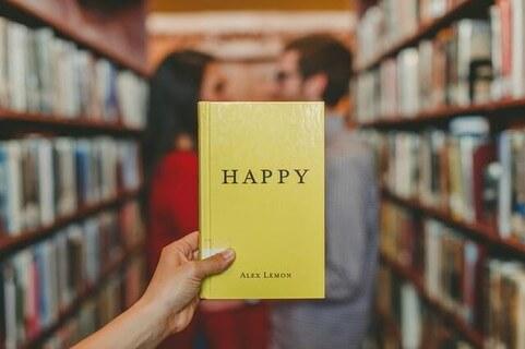図書館の本棚の間で幸せそうに話すカップルとHAPPYと書かれた黄色の本