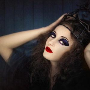 ハロウィンの仮装のために濃いメイクをほどこした黒いドレスの女性