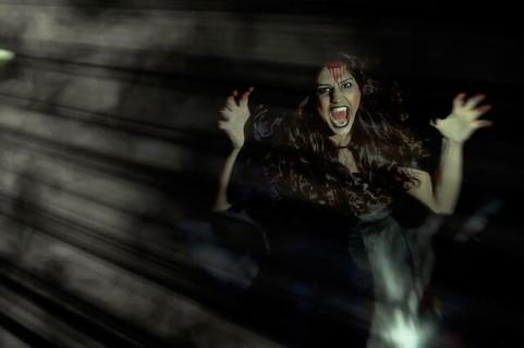 ヴァンパイアのコスプレをして暗闇の中で牙をむき出す女の子