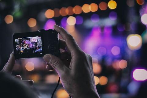 イベントのステージを一生懸命カメラで撮影する女性の手元