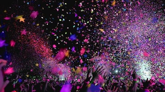 歓声を上げ盛り上がる人たちとカラフルな紙ふぶきに包まれるパーティー会場